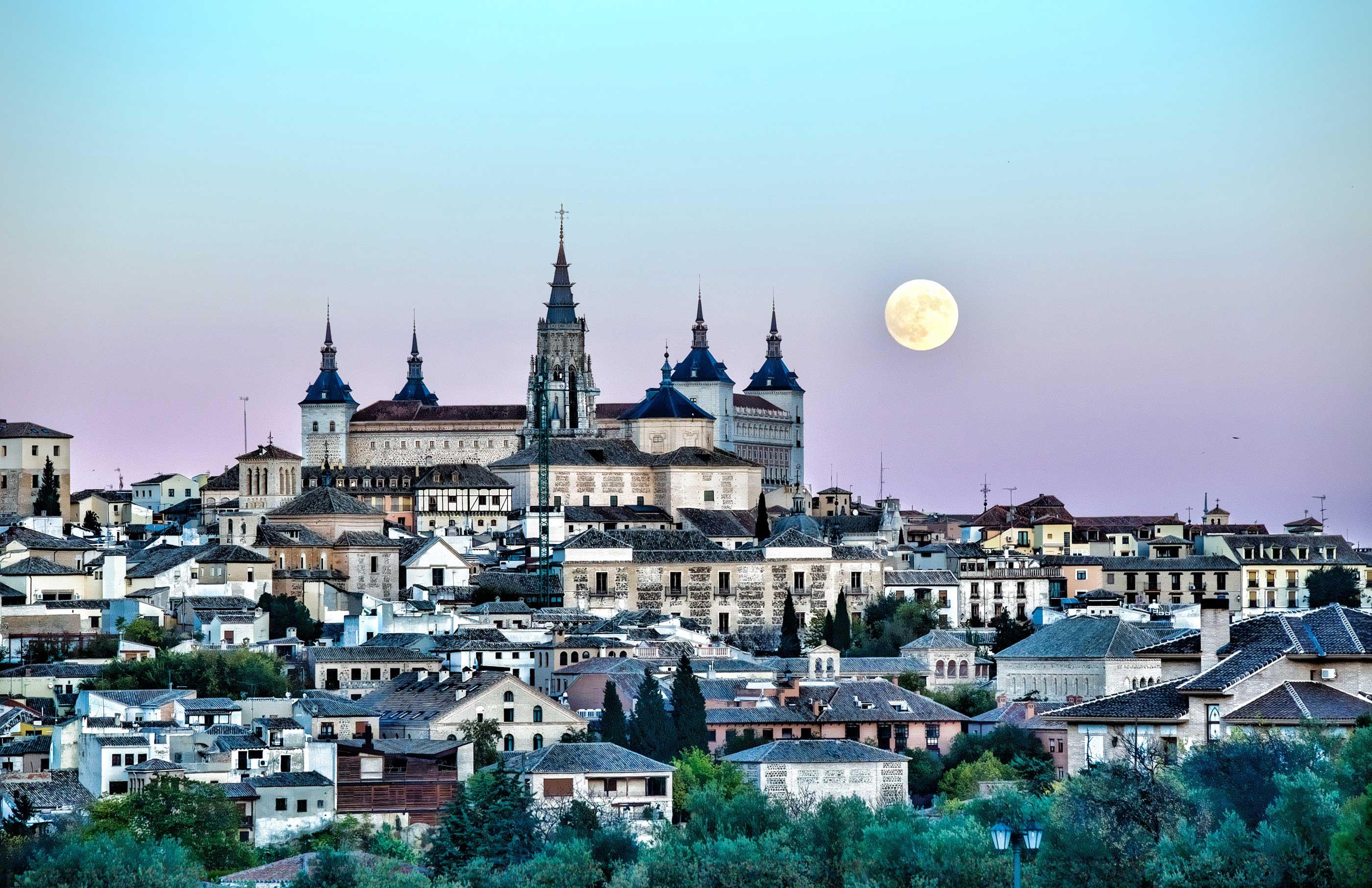 Vista panorámica de Toledo, al atardecer, con la torre de la Catedral y el Alcázar bajo una luna llena